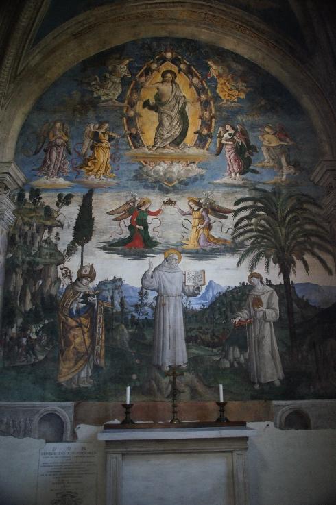Fresko in der Bufalini-Kapelle: Christus zwischen Engeln und der Heilige Bernhard von Siena mit weiteren HeiligenIn der Bufalini-Kapelle ist das Leben des hl. Bernhardin von Siena von Pinturicchio dargestellt. In diesem Ausschnitt ist Christus in der Mandorla, umgeben von Engeln, zu sehen.