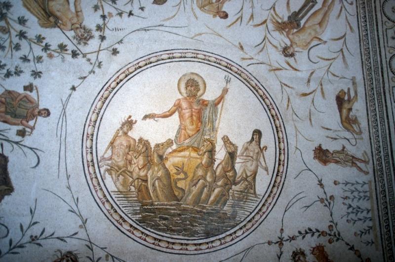 Jahreszeitenmosaik aus La Chebba (130-150 n. Chr.). Mittig Neptun auf einer Quadriga und in den Ecken die vier Jahreszeiten. Neptun gilt als Symbol der Fruchtbarkeit.