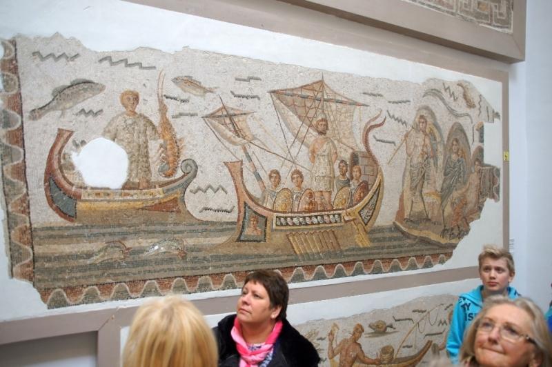 Ulysses (Odysseus) fährt an der Insel der Sirenen vorbei und lauscht ihren Gesängen. (3. Jhd. n. Chr.). Auf seiner Reise musste Odysseus an der Insel der Sirenen vorbei. Dort lebten Nymphen, halb Vogel, halb Mensch, die mit ihrem Gesang jeden Vorbeifahrenden verzauberten. Doch wer sich einmal durch den lieblichen Gesang zu ihnen herüberlocken ließ, der war verloren und musste sterben, so die Sage. Odysseus war gewarnt und verklebte seinen Gefährten die Ohren mit Wachs als sie sich der Insel näherten. Ihn selbst jedoch trieb die Neugierde, das Lied der Sirenen zu hören. Und so ließ er sich an den Mastbaum binden und befahl ihnen, egal wie er auch bitten und flehen möge, ihn nicht eher zu befreien, bis sie an der Insel vorbeigesegelt wären. Mosaik aus Dougga. Dougga ist ein Ort im tunesischen Gouvernement Beja. Im Rahmen der archäologischen Ausgrabungen wurden die Einwohner Douggas schrittweise umgesiedelt.