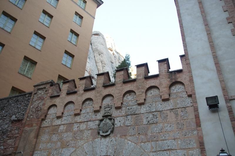 Man sieht hier das Montserrat Wappen von 1565, das über dem Torbogen ist, durch den wir über den Liebfrauensteig, der links und rechts Magnolien hat, auf den Platz kommen. Die Gebäude rund herum sind allesamt für die Pilger da, als Versorgungs- oder Beherbungsmöglichkeiten.
