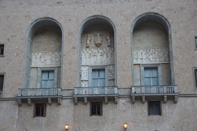 Die Fassade ist mit Steinen aus dem Gebirge selbst verkleidet. In den Arkaden sind Reliefs. Das linke ist der heilige Benedikt, als Vater des Mönchtums, in der Mitte die Verkündigung des Dogmas und Aufnahme Marias in den Himmel durch Papst Pius XII. und das rechte zeigt wieder den heiligen Georg umgeben von Mönchen, die im Bürgerkrieg 1936-1939 ums Leben kamen.