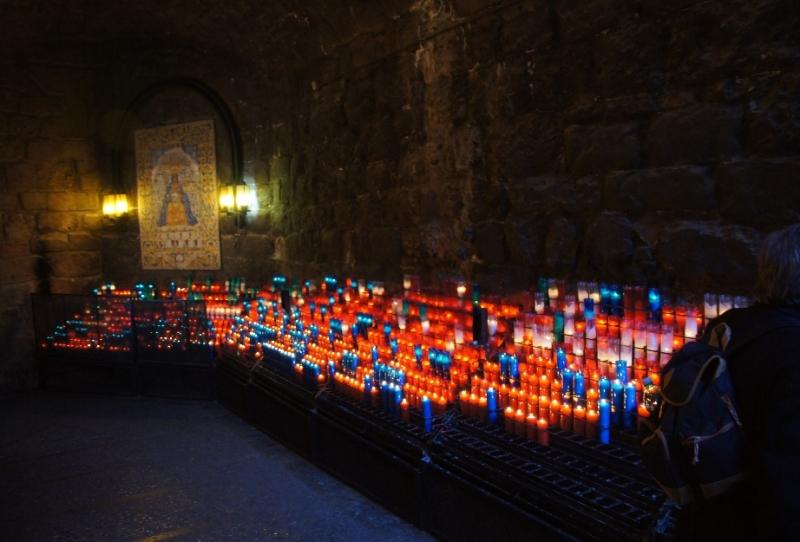 """Rechts Keramische Fliesen zu einem Bild der Schwarzen Madonna zusammengefügt. Wo so viele Kerzen stehen, da mussten wir natürlich auch eine dazustellen. Hier konnte man sehen, wie wichtig den Katalanen """"ihre Madonna"""" ist."""